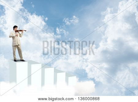 Young businessman standing on bars and playing violin