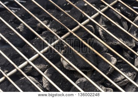 A charcoal grill closeup with the coals beginning to turn white.