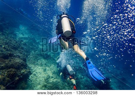 Air bubbles emerging from diver at coral reef under water