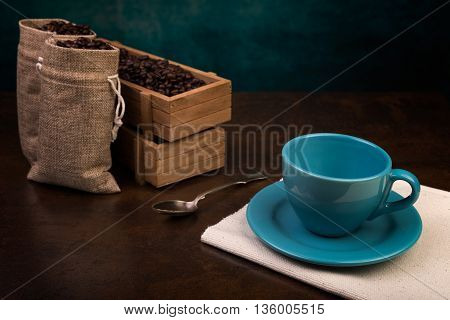 Empty cup of coffee and jute bags wooden containers filled with cofee beans on the rust background