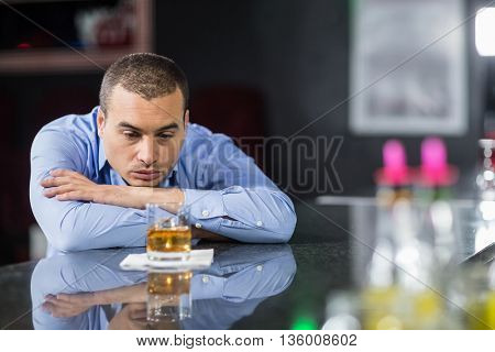 Depressed businessman looking at whisky glasses in a pub