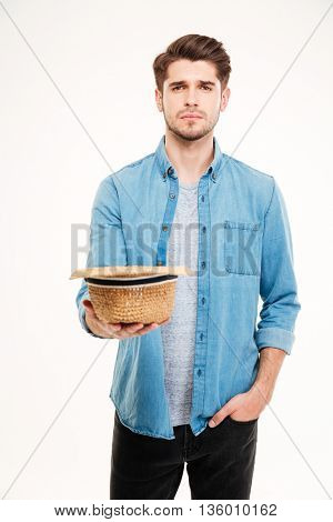 Sad poor young man holding hat and asking for money over white background