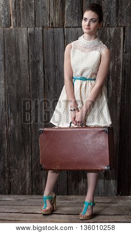 beautiful girl in white dress and suitcase in anticipation of trip