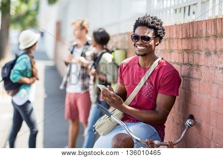Happy young man sitting on bicycle using mobile phone with friends interacting background
