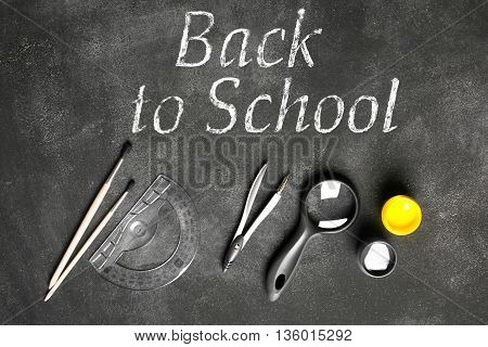 Back to school concept. Compass magnifying glass brushes on the black chalkboard. Back to scholl inscription on the board