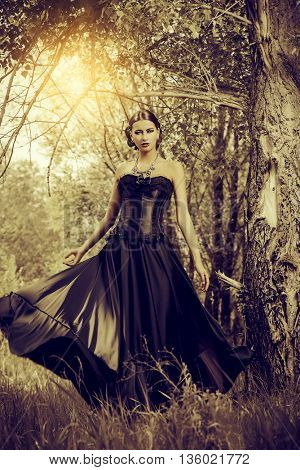 Magnificent brunette woman in black old-fashioned dress walking in the thicket of the magic forest. Gothic style. Fashion.