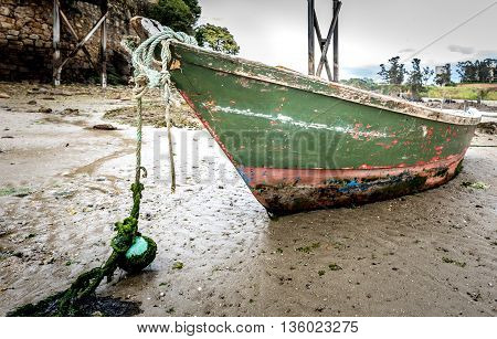 Old Fishing Boat Is Moored On Beach At Low Tide.