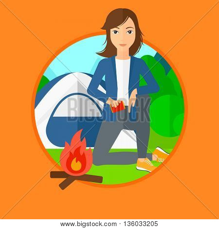 Woman kindling campfire on the background of camping site with tent. Tourist relaxing near campfire. Woman sitting near campfire. Vector flat design illustration in the circle isolated on background.