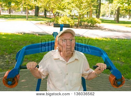 The surprised old man going in for sports on a street simulator in park