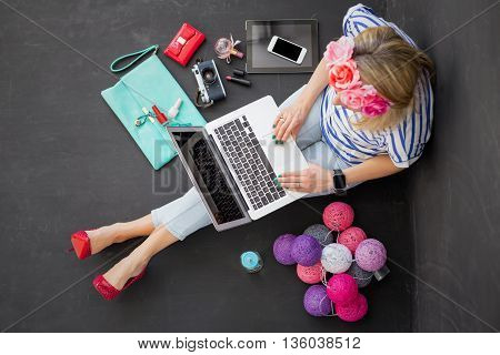 Modern woman sitting on the floor with computer in her lap