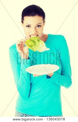 Fit young beautiful woman eating salat