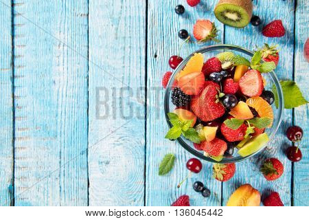 Fresh fruit salad with various kind of berry and citrus fruit served in glass bowl, placed on wooden table. Shot from aerial view, copyspace for text