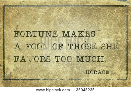 Fortune makes a fool of those she favors too much - ancient Roman poet Horace quote printed on grunge vintage cardboard