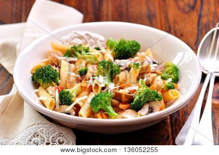 Pasta with chicken, broccoli, carrots, tomatoes and parmesan
