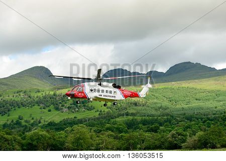 KILLIN SCOTLAND - JUNE 27 2016: HM Coastguard helicopter taking off from the refuelling point near the village of Killin in Perthshire Scotland.
