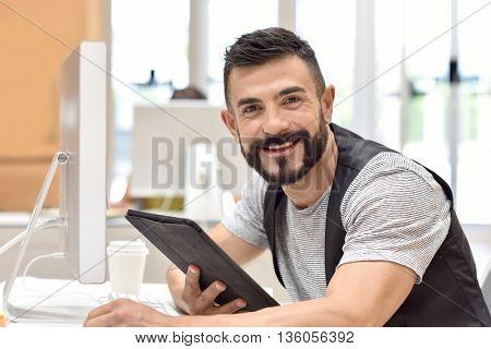 Trendy bearded guy in office websurfing on tablet