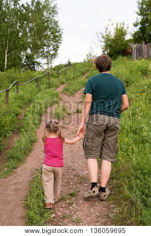 Father and daughter walking on a hill. They are standing backward to the camera walking up.