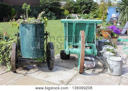 An english garden with a vintage water carrier and wheel barrow being used as planters for flowers