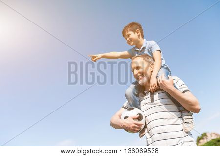 Cheerful grandfather and child are resting in the nature and smiling. The boy is sitting on male shoulders and pointing finger forward with interest. Mature man is standing and holding ball