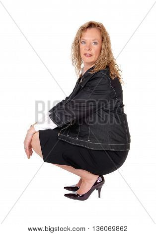 A beautiful blond woman crouching on the floor in a black skirt and navy jacket isolated for white background.