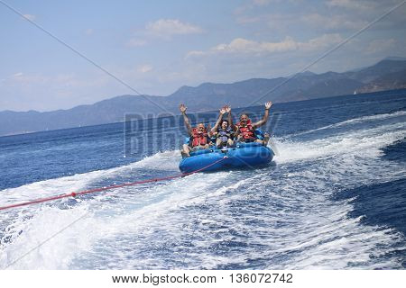 25TH MAY 2016, FETHIYE, TURKEY: English tourists having fun riding in inflatables being pulled by a speedboat in a bay at Fethiye ,Turkey, 25th may 2016