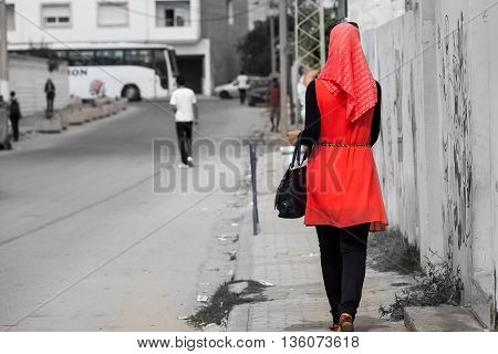 Modest fashionable young eastern Arabic woman walking down gray street in brilliant red dress