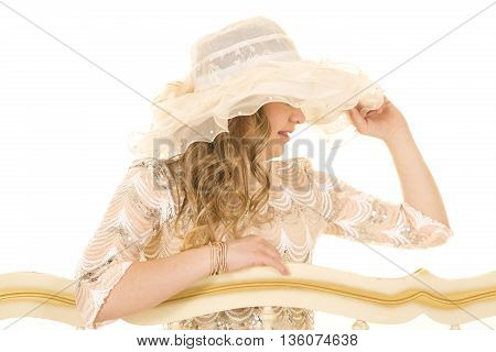 a woman with down syndrome touching her lace hat looking to the side.