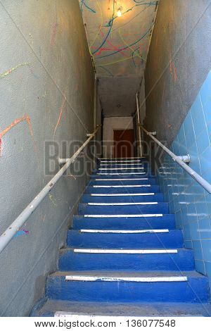 A flight of stairs leads to a second floor entrance on a decaying urban street.