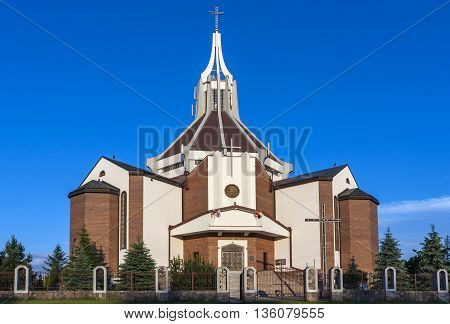 The modern Catholic church built of red brick.