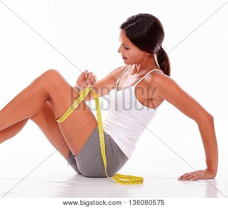 Isolated Young Brunette Measuring Her Thigh
