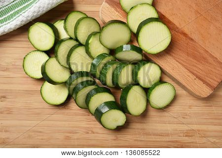 Overhead view of sliced zucchini on a cutting board