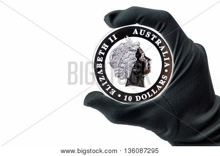 Hand in black glove holding large silver 10 dollars coin