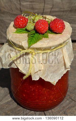 Jar of raspberry jam and fresh raspberries