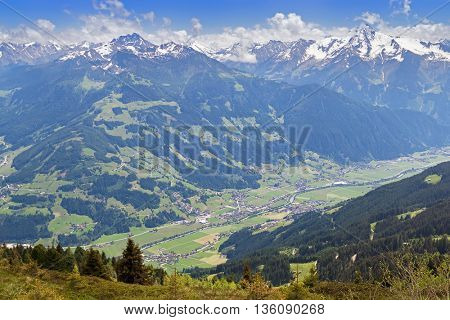 Bird view of the Zillertal valley village surrounded by mountains with snow during summer in Tyrol, Austria, Europe