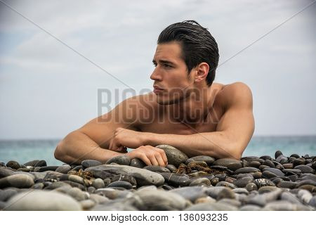 Attractive muscular young shirtless athletic man laying down on pebbles in front of water by sea or ocean shore, looking to a side in a cloudy summer day