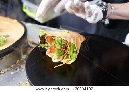 Making vegetable crepe, roll with tomatoes and lettuce. Salty crepe or pancake with fillings made by street vendor's hands at outdoors creperie. French cuisine, cooking for commercial kitchen.