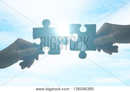 Partnership concept with hands putting puzzle pieces together on sky background with sunlight