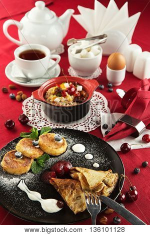 Breakfast with pancakes with jam, cheesecakes, porridge with candied fruits, berries and nuts, a boiled egg cup of and tea on a laid table