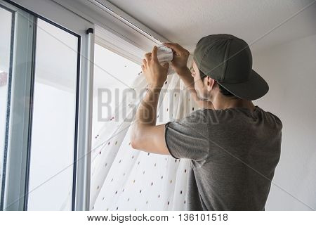 Young handsome man or handyman installing curtains over window at home, doing renovation work