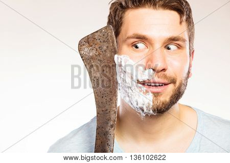 Young man with shaving cream foam on half of face having fun with machete large knife. Handsome guy removing beard hair. Skin care and hygiene humor.