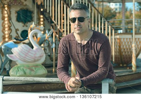 Handsome man over park with carousel. Outdoor male portrait.