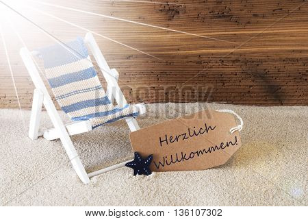 Sunny Summer Label With Sand And Aged Wooden Background. German Text Herzlich Willkommen Means Welcome. Deck Chair For Holiday Or Vacation Feeling.
