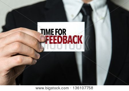 Business man holding a card with the text: Time for Feedback