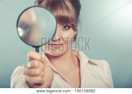 Investigation exploration education concept. Closeup woman holding magnifying glass loupe in hand filtered photo poster