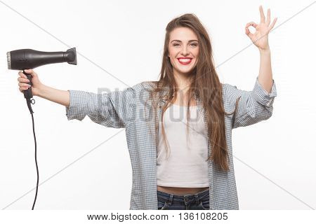 Beautiful woman drying her hair in studio. Happy woman wuth red lips looking at camera, showing okay sign and holding hair dryer isolated on white background.