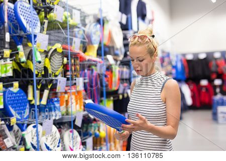 Beautiful caucasian woman shopping sports equipment in sportswear store.