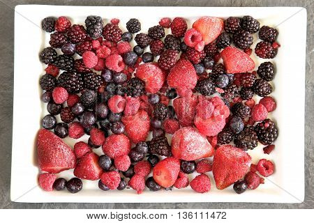 Frozen mixed berries on a white plate.