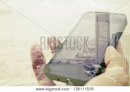 Double exposure image of using smart phone with cityscape background