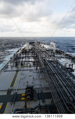 Crude oil tanker forward part of the deck with pipe line in the sea.