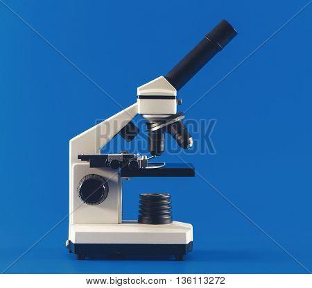monocular microscope on blue background. Toned image